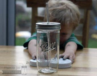 Glass straw in pint-and-a-half wide mouth Mason jar with metal daisy hole lid