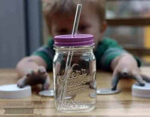 Glass straw in pint Mason jar with pink straw hole lid