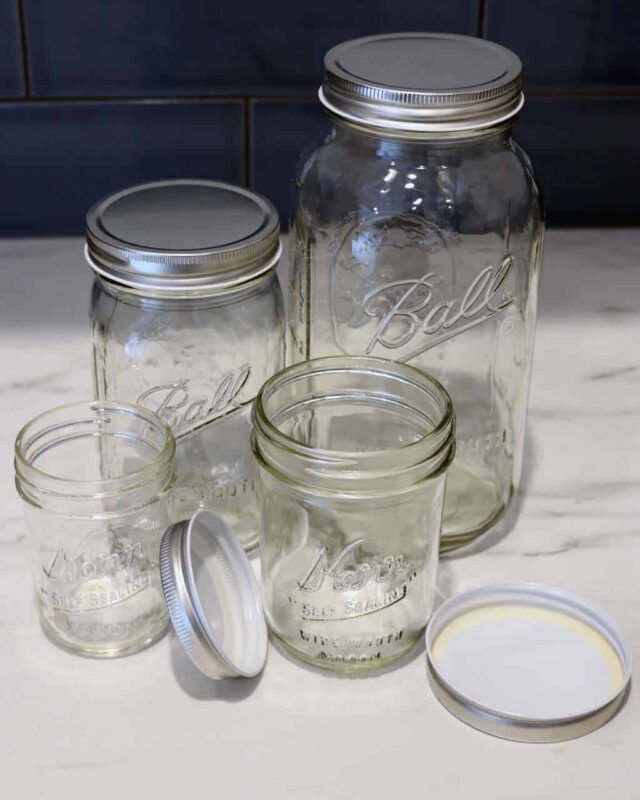 Shiny silver storage lids on half pint, pint, quart, and half gallon Ball and Kerr Mason jars