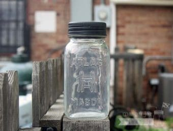 Solar light lid in black on Atlas Mason jar on fence post