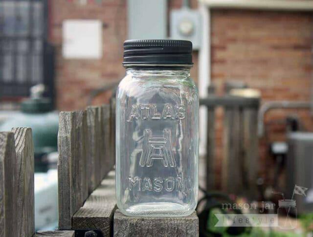 Solar light lid in black on Atlas Mason jar on fence post