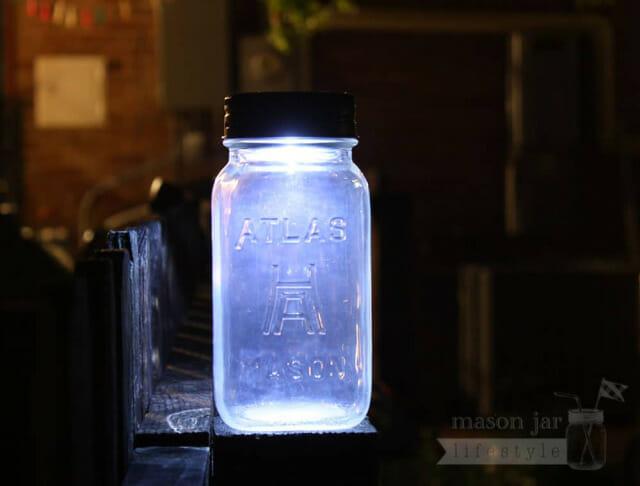 Solar light lid on Atlas Mason jar on fence post at night