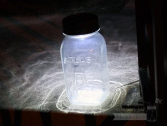 Solar light lid on Atlas Mason jar on front steps at night