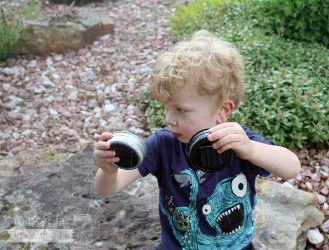Boy holding solar light lids in black and silver for regular mouth Mason jars