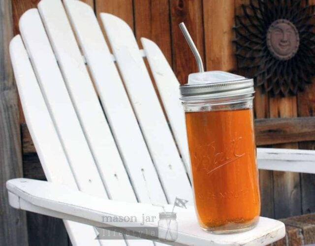 Pint and a half jar with stainless steel straw on an Adirondack chair