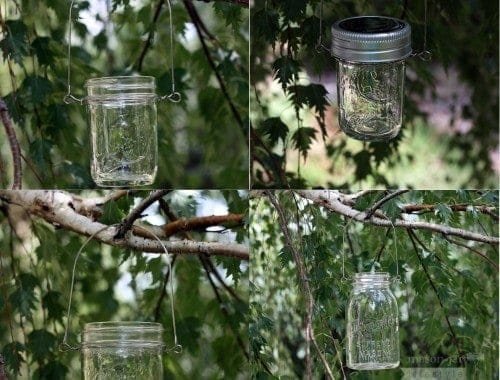 Four Mason jars with stainless steel wire handles hanging in birch tree