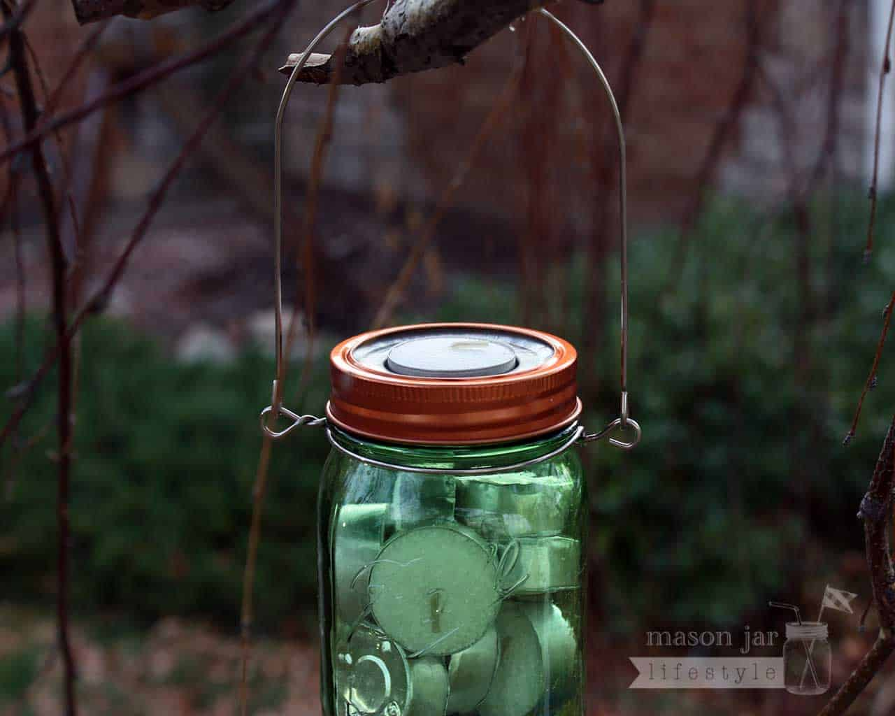 metal tea light candle holder insert with copper band and stainless steel wire handle on tree