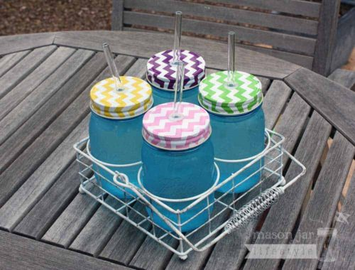 Vintage white caddy for 4 pint Ball Mason jars with chevron lids and glass straws on table
