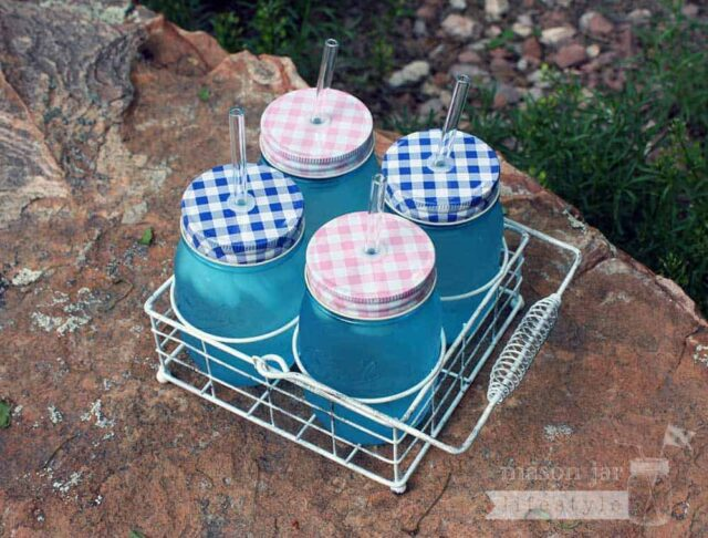 Vintage white caddy for 4 pint Ball Mason jars with gingham lids and glass straws top view
