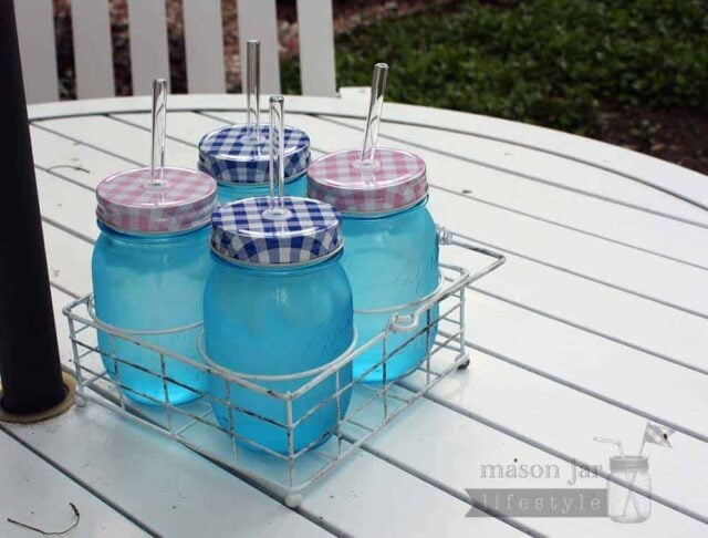 Vintage white caddy for 4 pint Ball Mason jars with gingham lids and glass straws on table