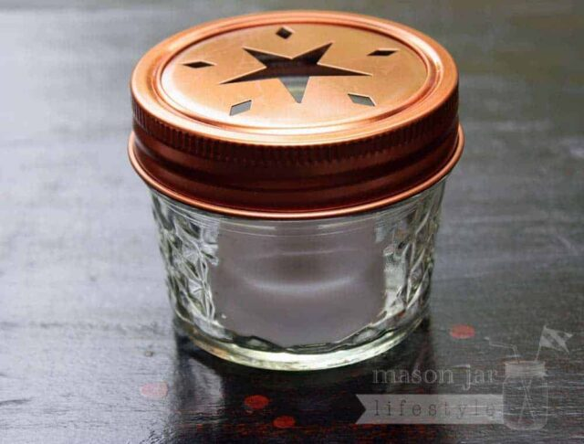 Copper star cutout lid and band on 4oz Ball jelly jar with tea light