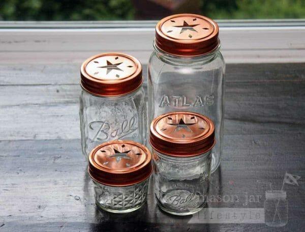 Copper star cutout lids and bands on 4 Ball Mason jars - a 4oz jelly jar, half pint jar, pint jar, and quart jar