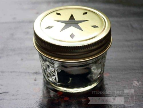 Gold star cutout lid and band on 4oz Ball jelly jar with tea light