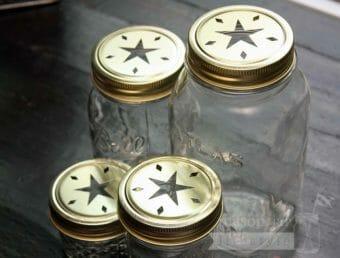 Gold star cutout lids and bands on 4 Ball Mason jars - a 4oz jelly jar, half pint jar, pint jar, and quart jar