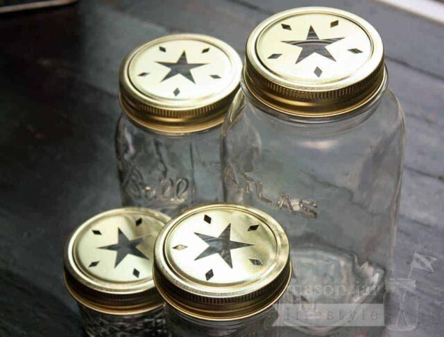 Gold star cutout lids and bands on 4 Ball Mason jars - a 4oz jelly jar, half pint jar, pint jar, and quart jar