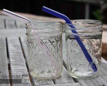 Two half pint Ball jars with pink and blue glass straws