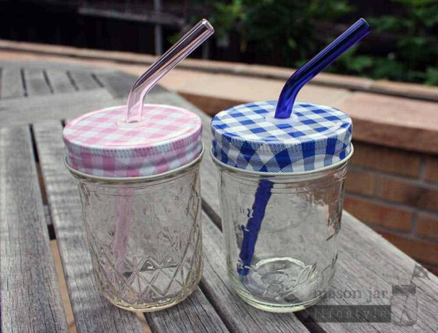 Two half pint Ball jars with pink and blue glass straws and gingham tumbler lids