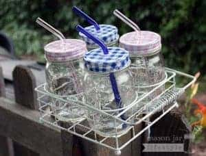 Carrying caddy for 4 pint jars with pink and blue glass straws and gingham lids