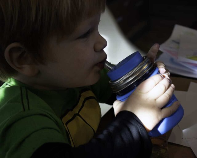 Boy drinking from half pint 8oz Mason jar with silicone straw, sleeve, and lid