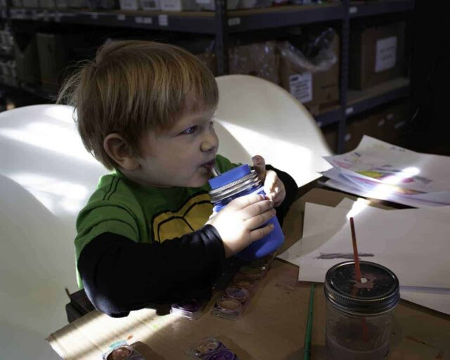 Boy painting and drinking from half pint 8oz Mason jar with silicone straw, sleeve, and lid