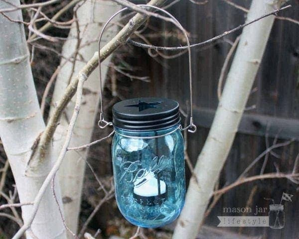 Star cutout tea light candle holder in blue Ball Mason jar with wire handle in tree