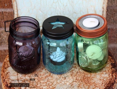 Three types of tea light candle holders on green, blue, and purple Ball Mason jars on rusty chair