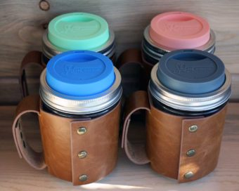 Back view of four wide mouth pint Mason jars with leather sleeves and silicone drinking lids