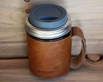 Charcoal gray silicone drinking lid and faux leather sleeve with handle on wide mouth pint Mason jar