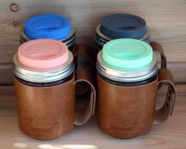 Four wide mouth pint Mason jars with leather sleeves and silicone drinking lids