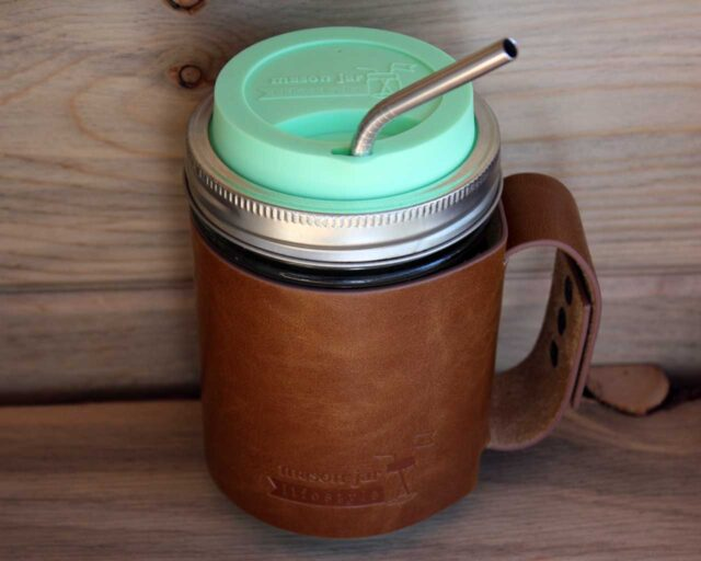 Mint green silicone drinking lid, thin bent stainless steel straw, and faux leather sleeve with handle on wide mouth pint Mason jar