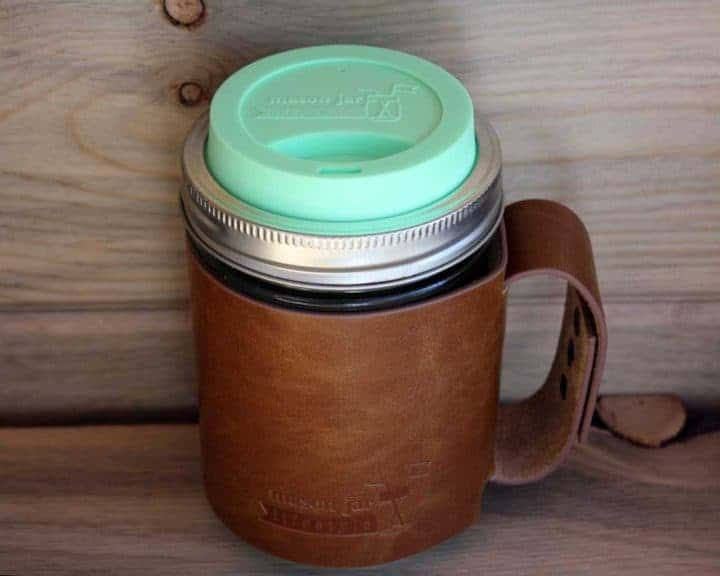 Mint green silicone drinking lid and faux leather sleeve with handle on wide mouth pint Mason jar