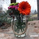 Thick rope handle on wide mouth quart Mason jar with flowers sitting on rock