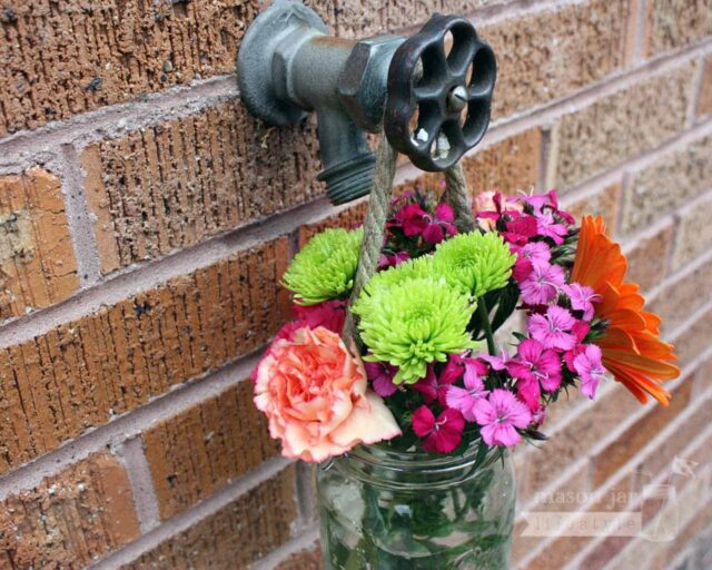 Thin rope handle on wide mouth quart Mason jar with flowers hanging on water faucet