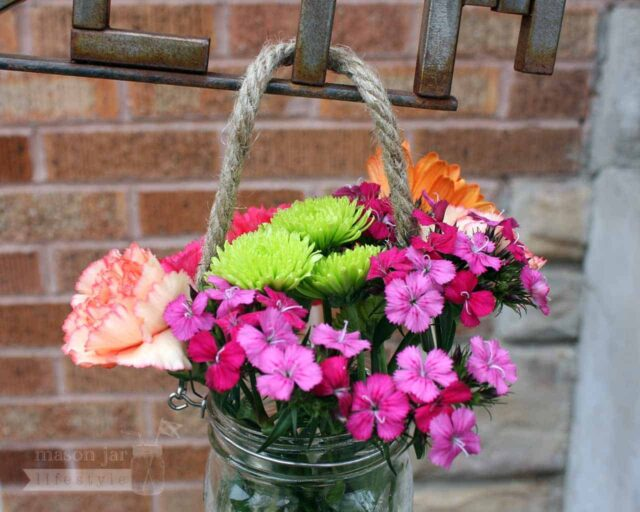 Thin rope handle on wide mouth quart Mason jar with flowers hanging on sign