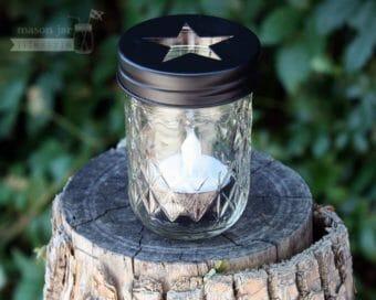 Black star tea light candle holder in half pint jelly jar on log