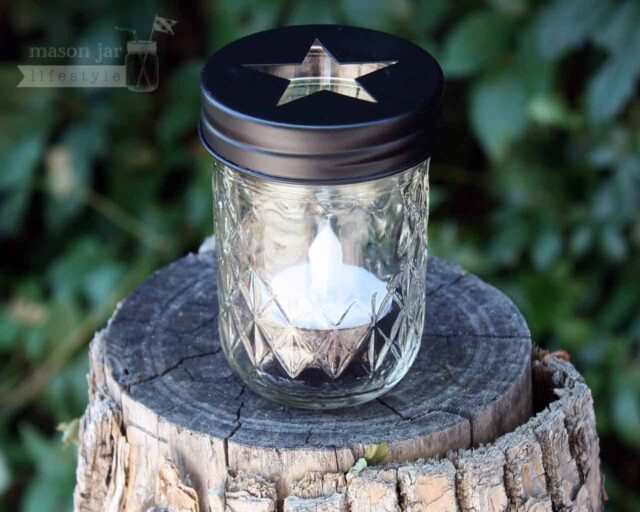 Black star tea light candle holder in half pint jelly jar on log