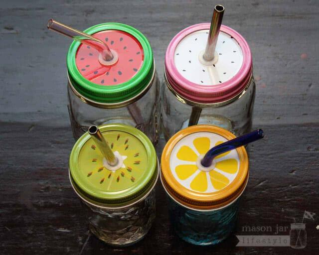 Fruit tumbler lids with straws in regular mouth Mason jars - watermelon, dragon fruit, kiwi, and lemon