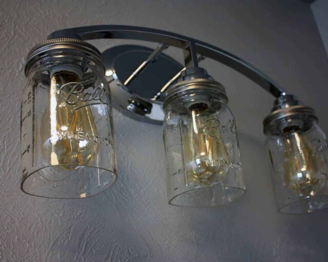 Light fixture with three quart cut bottom Ball Mason jars, wide mouth lighting lids, and LED Edison bulbs