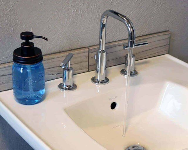 Oil rubbed bronze soap pump dispenser lid kit on blue Ball Mason pint jar on sink with running water