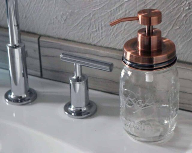 Vintage copper soap pump dispenser lid kit on Ball Mason pint jar on sink