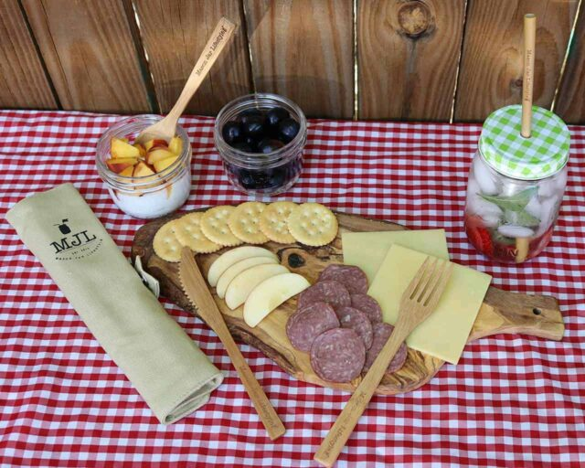 mason-jar-lifestyle-bamboo-utensil-set-roll-up-cotton-carrying-bag-fork-knife-straw-pint-jar-gingham-lid-cutting-board-cheese-apples-salami-crackers